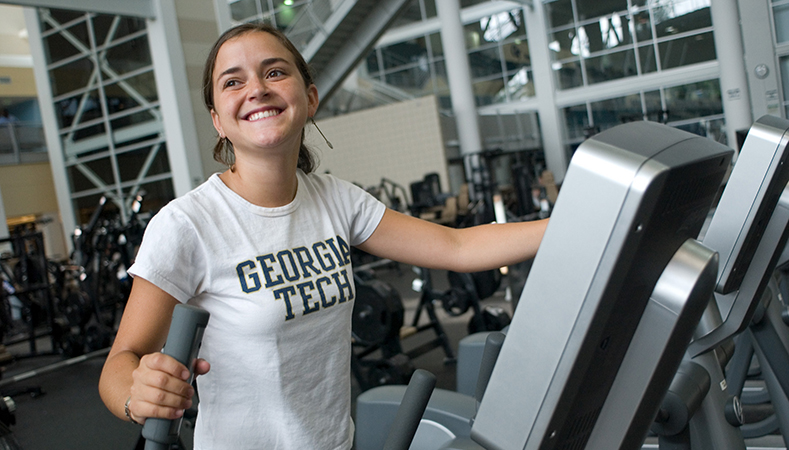 A Georgia Tech student smiling and working out at the gym