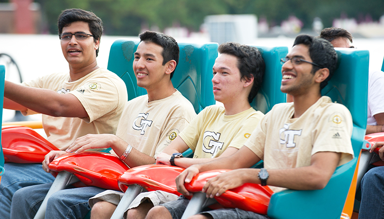 Men from a student organization riding a rollercoaster